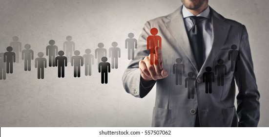 Businessman having small icon people in his hand