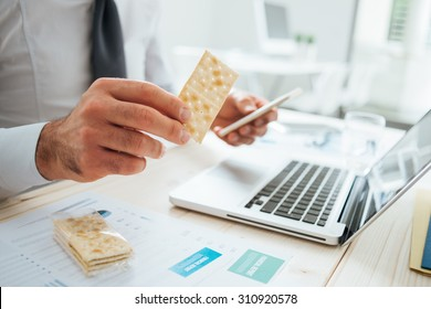 Businessman having a snack at desk holding a cracker and a smart phone, hands close up, unrecognizable person