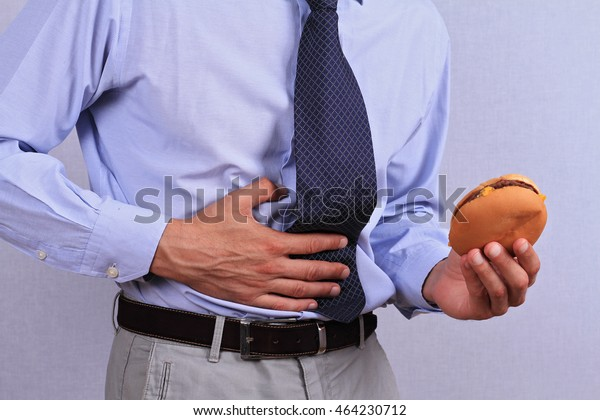 Businessman having stomachache because of eating junk food. Chronic gastritis or Ulcer.