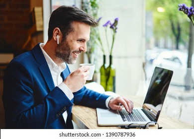 Businessman having videocall on laptop while drinking coffee in cafe