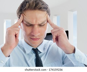 Businessman with a headache against bright white room with windows