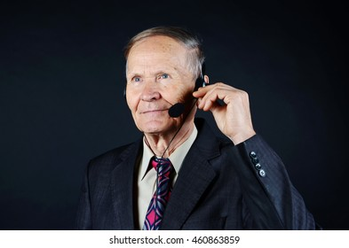 Businessman with headphones, on line service, call center man on black background