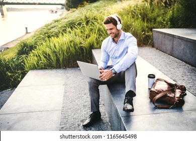 A businessman with headphones sitting outdoors on stairs, using laptop.