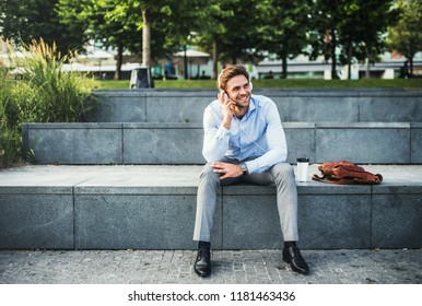 A businessman with headphones sitting outdoors on stairs, listening to music.