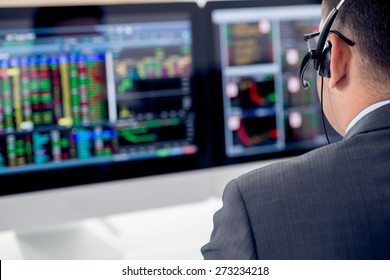 Businessman in a headset looking at the statistics of stock exchange, view over the shoulder