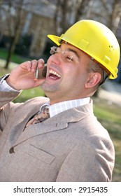 A businessman with helmet calling by mobile phone