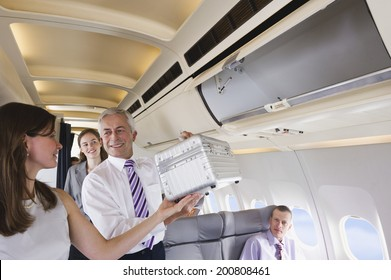 Businessman helping a businesswoman packing baggage in overhead locker on airplane