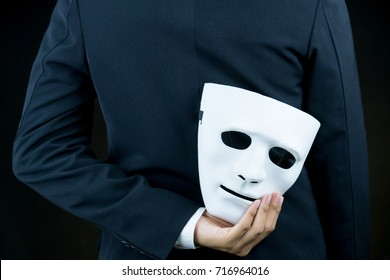 businessman hide the white mask in the hand behind his back on black background.