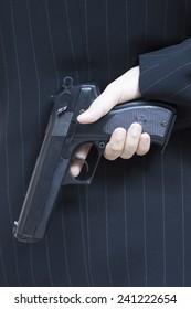 businessman hiding a gun behind his back