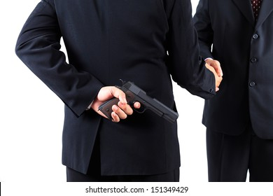 Businessman hiding gun while handshaking concept for dishonesty