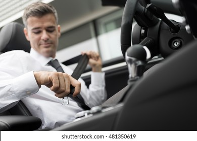 Businessman in his car fastening the seatbelt, safe driving concept