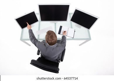Businessman in his clean high tech office looking on the monitors upper view