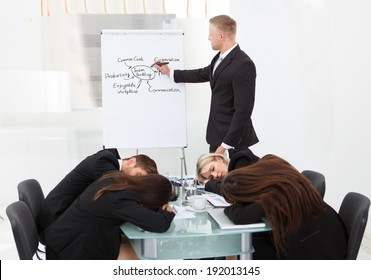 Businessman And His Colleagues Sleeping During Presentation
