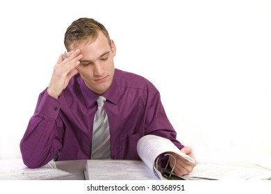 Businessman at his desk in the office thinks. He looks worried while on a file folder.