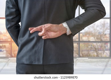 Businessman with his fingers crossed behind his back in the office