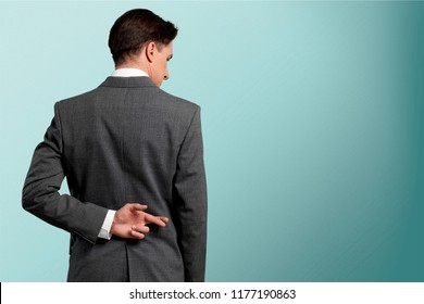 Businessman with his fingers crossed behind his back - concept for good luck or dishones