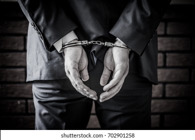 Businessman and his hands on the back handcuffed because of crime and corruption in business world. Arrested for outlaw with bricks in background. Black and white