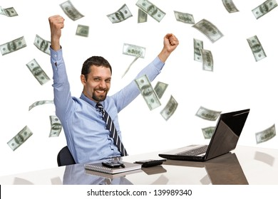 businessman with his hands raised while working on laptop with money rain