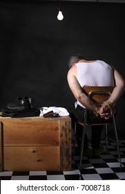 Businessman with his hands tied up sitting under a bare lightbulb in a hostage or kidnap situation.