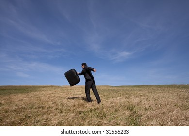 businessman with his luggage outdoor in the field