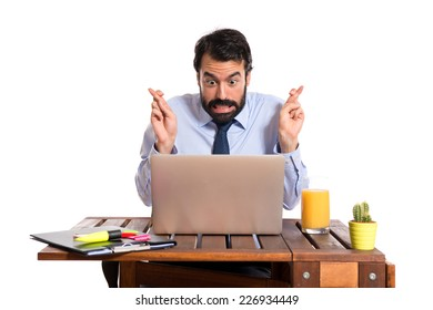 Businessman in his office with his fingers crossing