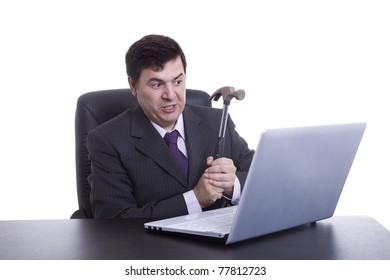 Businessman in his office threatening to destroy his PC with a hammer