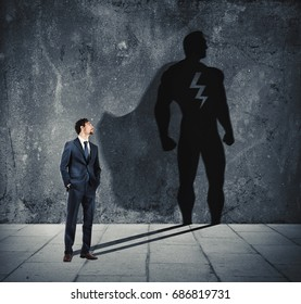 Businessman with his shadow of super hero on the wall. Concept of powerful man