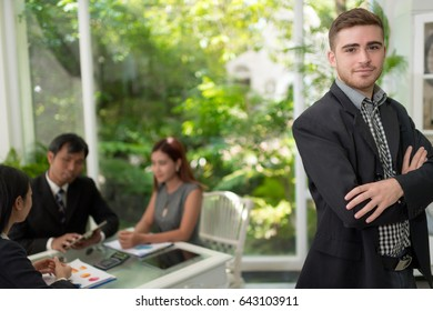 businessman with his staff, people group in background at modern garden home office indoors
