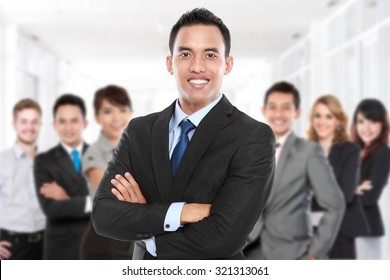 Businessman with his team member behind. smiling with crossed arms