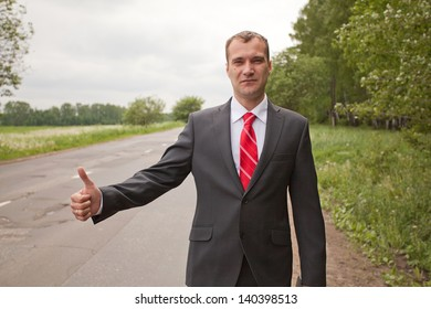 Businessman hitchhiking on a road