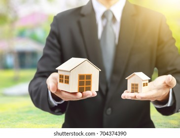 businessman hold big and small houses on hand