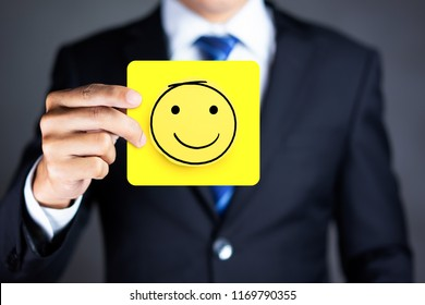Businessman hold a happy face icon drawn on paper, Customer experience and satisfaction survey concept