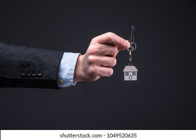 Businessman hold key with key ring of a house. Concept for the housing market