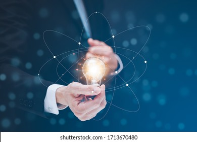 Businessman hold the light bulb in graph Screen Icon of media screen,Technology Process System Business concept.