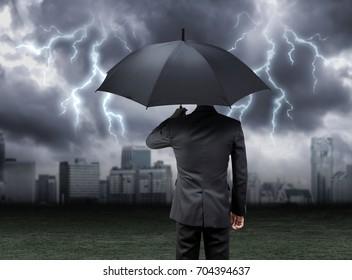 businessman hold umbrella under rain with city background