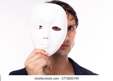 Businessman hold white mask in his hand. Man is dishonest cheating person. Faking, cheating business partnership, dishonest hiding in mask. Cheating person take off his mask and revealed the real him