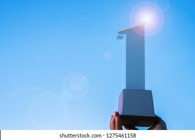 Businessman holding 1st award trophy Number one show first, best success achievement and prize of business as winner competition with blue sky shiny flare light background, copyspace for text