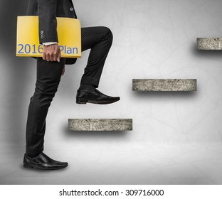 Businessman holding 2016 plan files and stepping up on stairs to success concept