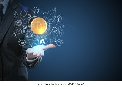 Businessman holding abstract digital bitcoin hologram on blue background. Innovation and cryptocurrency concept
