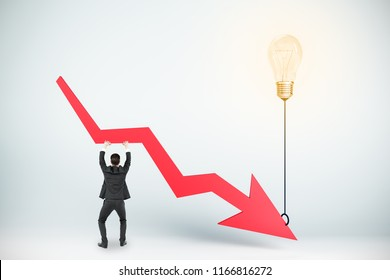 Businessman holding abstract downward arrow attached to glowing lamp balloon. Economy and decrease concept.