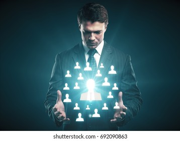 Businessman holding abstract glowing HR hologram on dark background. Hiring concept.