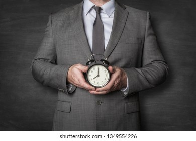 Businessman holding alarm clock in front of him