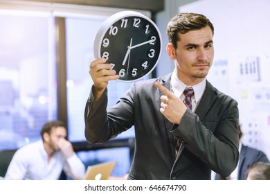 Businessman holding alarm clock in the hands in office.