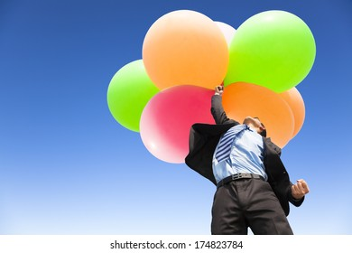 businessman holding balloons and flying up