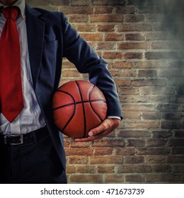 businessman holding a basketball on brick wall background