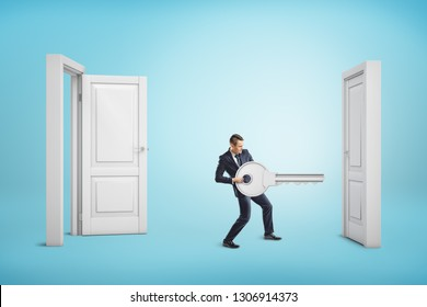 Businessman holding big key between an open door and a closed one on blue background. Business and management. Way to success. Taking chances.