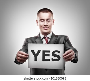 "businessman holding a billboard with inscription ""YES"""