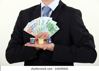 Businessman holding bills and toy blocks