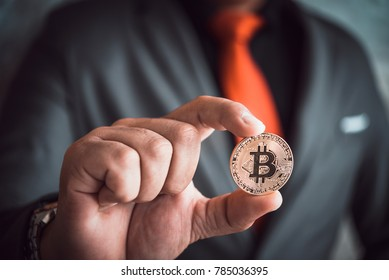 Businessman holding bitcoin in hand, bit coin BTC the new virtual electronic money, investment concept