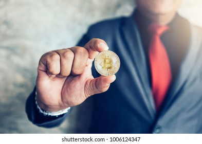 Businessman holding Bitcoin,Financial concept with golden Bitcoin.